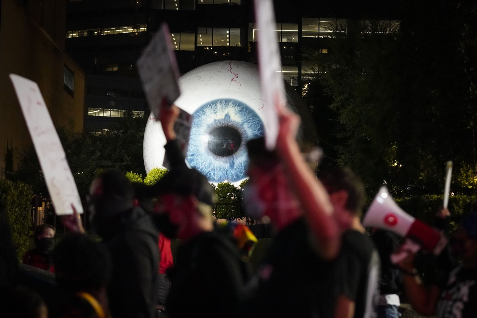 "Demonstrators pass artist Tony Tasset's giant eyeball sculpture, ""Eye"" on Main Street as they march in downtown Dallas after a Kentucky grand jury brought no charges against Louisville police for the killing of Breonna Taylor on Wednesday, Sept. 23, 2020."