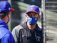Texas Rangers manager Chris Woodward talks with bench coach Don Wakamatsu before of a spring training game against the Kansas City Royals at Surprise Stadium on Sunday, Feb. 28, 2021, in Surprise, Ariz.