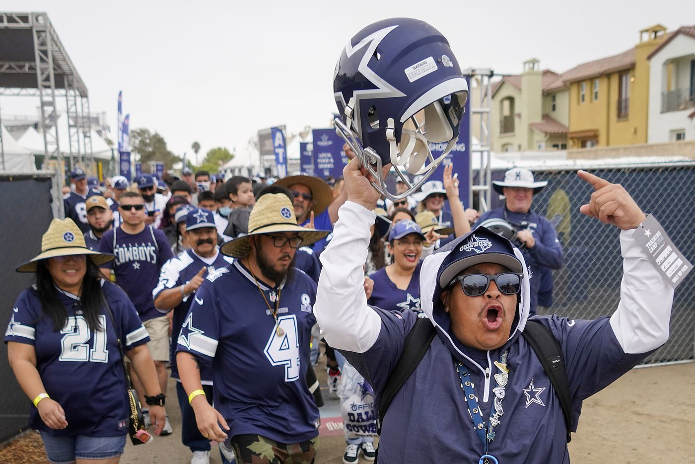 Dallas Cowboys fan Patrick Milan celebrates as the first one through the gates for a practice at training camp on Sunday, July 25, 2021, in Oxnard, Calif.