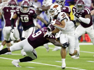 Oklahoma State running back Chuba Hubbard (30) is caught by Texas A&M defensive back Leon O'Neal Jr. (9) during the first half of the Texas Bowl NCAA college football game Friday, Dec. 27, 2019, in Houston.