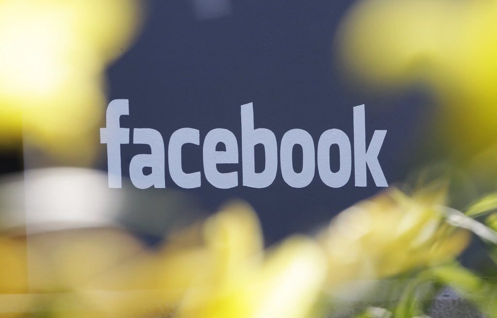 This Friday, May 18, 2012, file photo shows a sign at Facebook's headquarters behind flowers in Menlo Park, California. (AP Photo/Paul Sakuma, File)