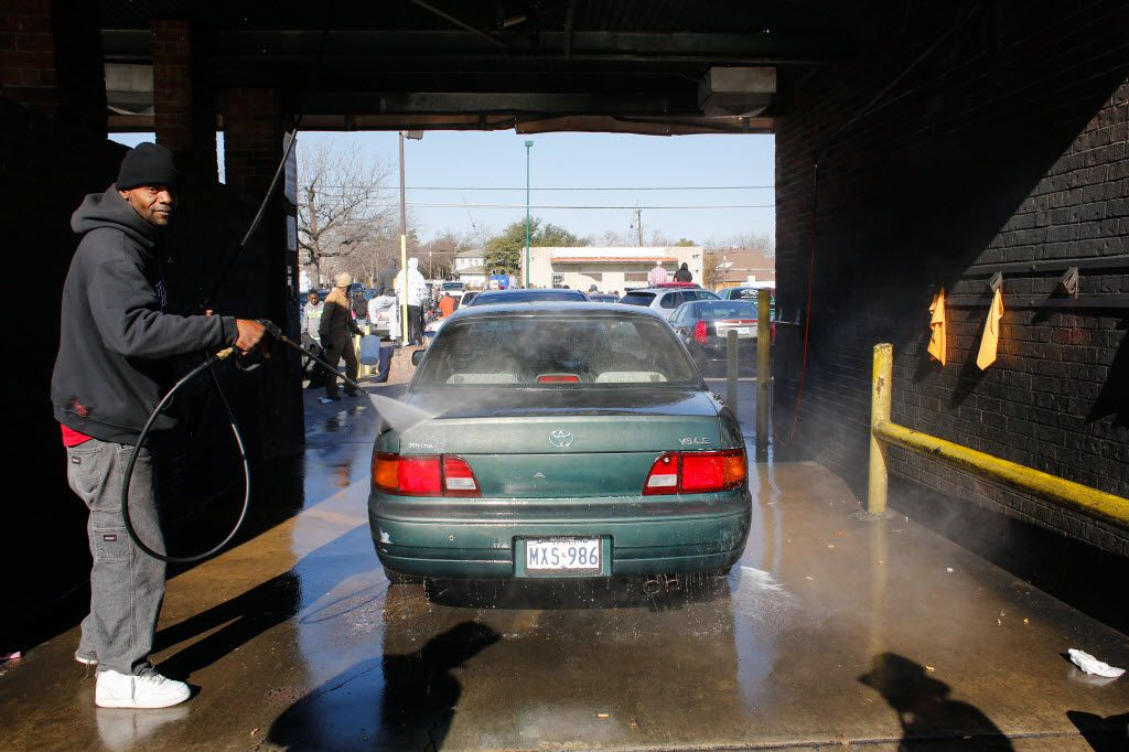 Orece Tasby takes advantage of the crowd by washing spectators' cars for tip money at Jim's Car Wash during the 27th Annual Elite News Martin Luther King Jr. parade in Dallas, Texas, on January 21, 2013.  (Stan Olszewski/The Dallas Morning News)