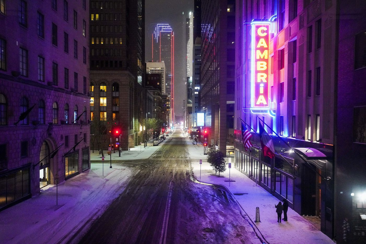 Elm Street is quiet in front of the Cambria Hotel as a winter storm brings snow and freezing temperatures to North Texas on Sunday, Feb. 14, 2021, in Dallas.  Sleet and light snow have arrived in North Texas early Sunday ahead of what is expected to be one of the worst winter storms in recent memory.