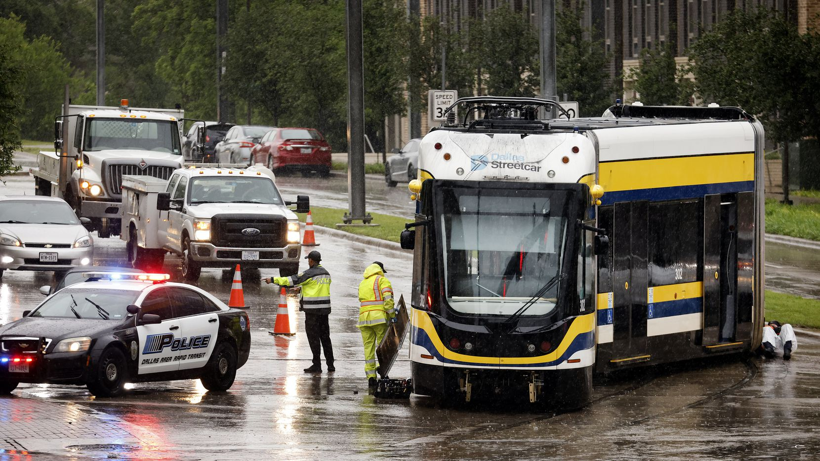 Working in the rain, DART crewman work on getting the Dallas Streetcar back on the tracks after a derailment at Zang Blvd. and Davis Street in the Bishop Arts District of Dallas, Tuesday, May 11, 2021. There were no injuries.  A shuttle bus is in place to provide transportation for customers, a spokesperson said. (Tom Fox/The Dallas Morning News)