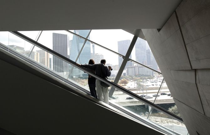 A couple enjoys the view as they ride the escalator at he Perot Museum of Nature and Science in Dallas.
