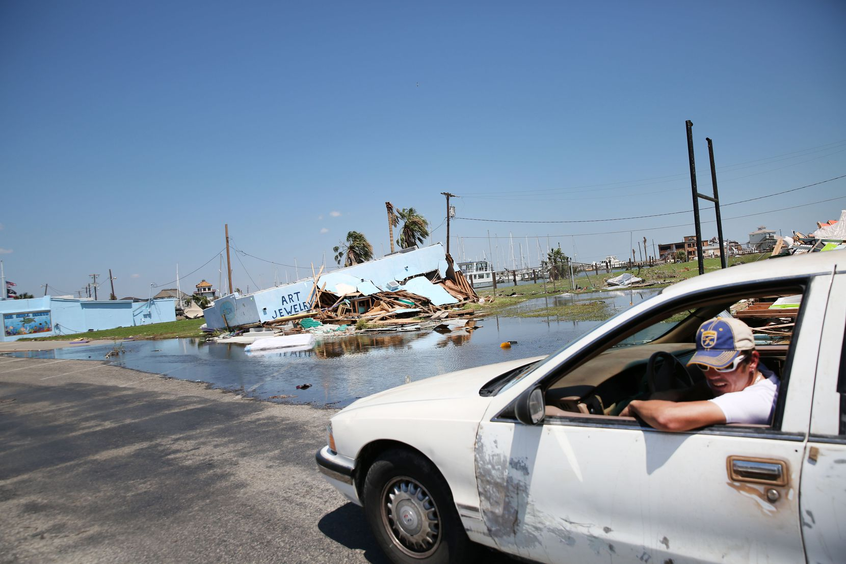 A man drives down South Austin Street in downtown Rockport, Texas on Wednesday, Aug. 30, 2017. The coastal region suffered severe damage after Hurricane Harvey hit the area on Aug. 26, 2017.