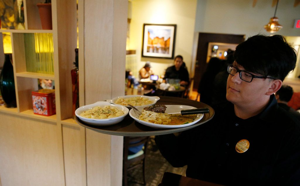 Salomon Guerra takes a tray of plates to customers at Olive Garden in Dallas, on Monday, August 6, 2018. Olive Garden is one of the few national chains to open a location in Oak Cliff, south of I-30.