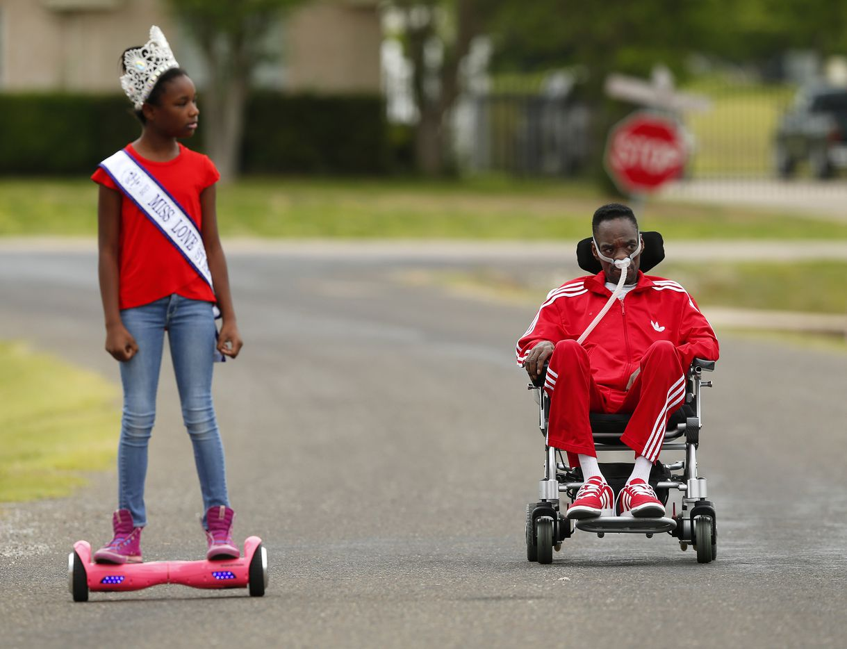 He in his wheelchair, she on her hoverboard - Alana Dixon and her father Rickey Dixon take a stroll in their Red Oak, Texas, Sunday, April 9, 2017. (Tom Fox/The Dallas Morning News)