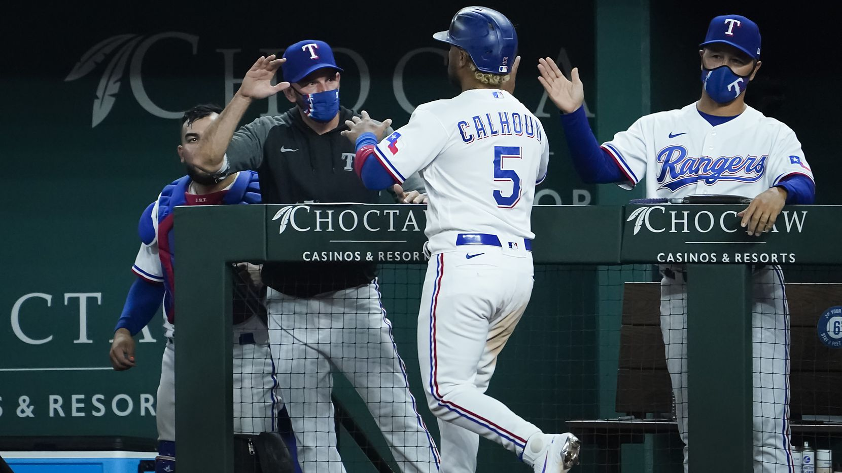 Texas Rangers designated hitter Willie Calhoun celebrates with Texas Rangers manager Chris Woodward and bench coach Don Wakamatsu after scoring during the eighth inning against the Boston Red Sox at Globe Life Field on Saturday, May 1, 2021.