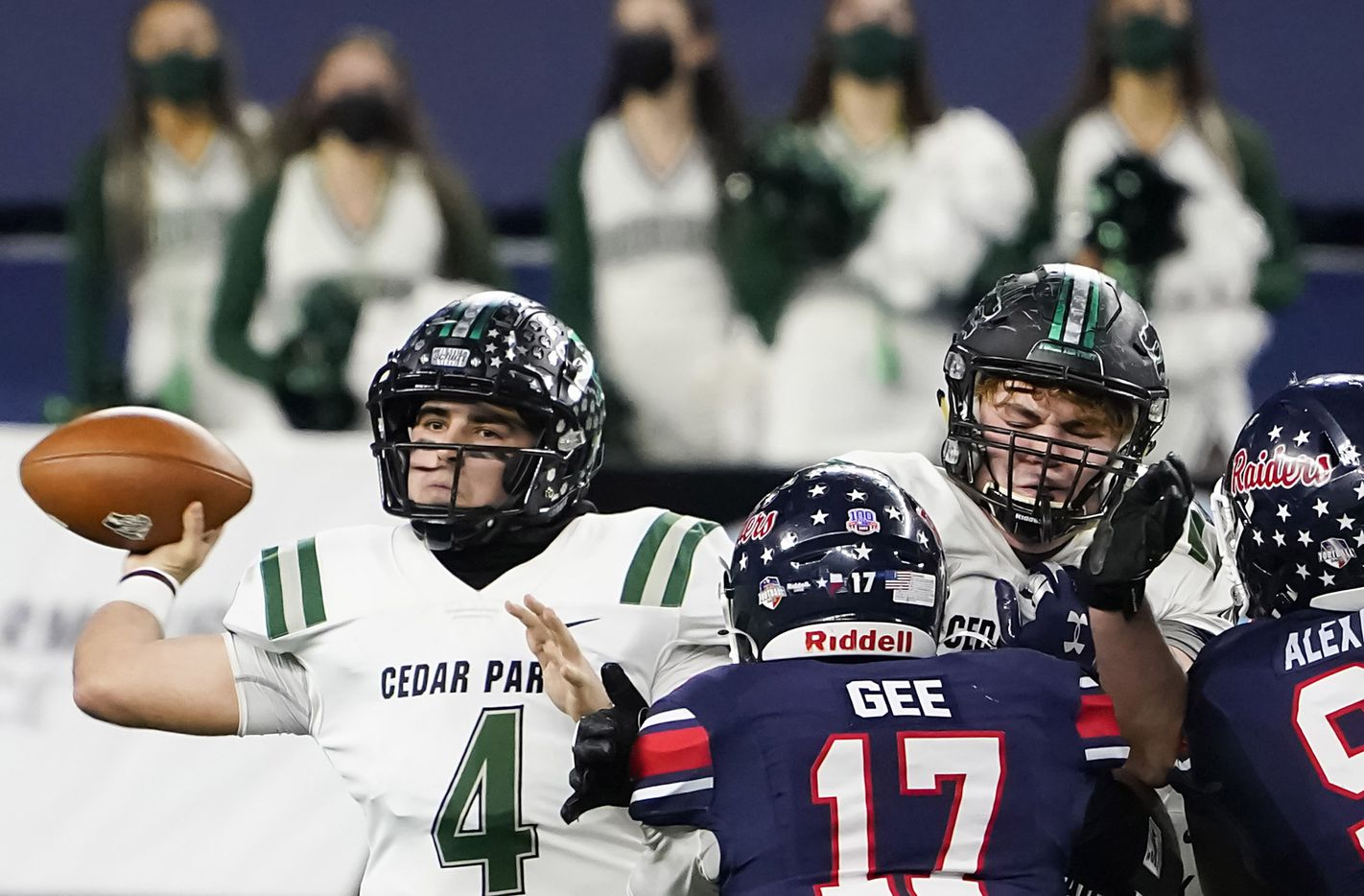Cedar Park quarterback Ryder Hernandez (4) gets off a pass under pressure from Denton Ryan defensive lineman Michael Gee (17) during the first half of the Class 5A Division I state football championship game at AT&T Stadium on Friday, Jan. 15, 2021, in Arlington, Texas. (Smiley N. Pool/The Dallas Morning News)