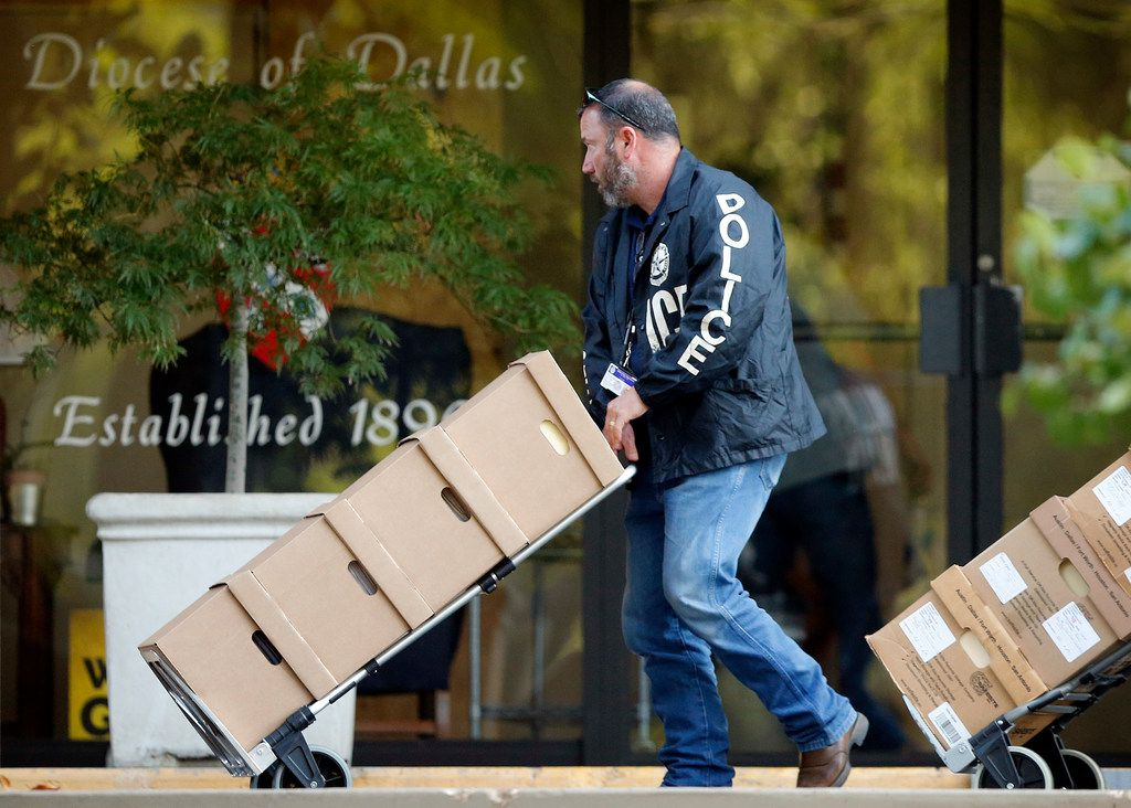 Dallas police cart out boxes from a raid on the Catholic Diocese of Dallas on Wednesday. Dallas police officers  raided several Dallas Catholic Diocese offices after a detective said church officials have not cooperated with investigations into sexual abuse by its past clergy members.