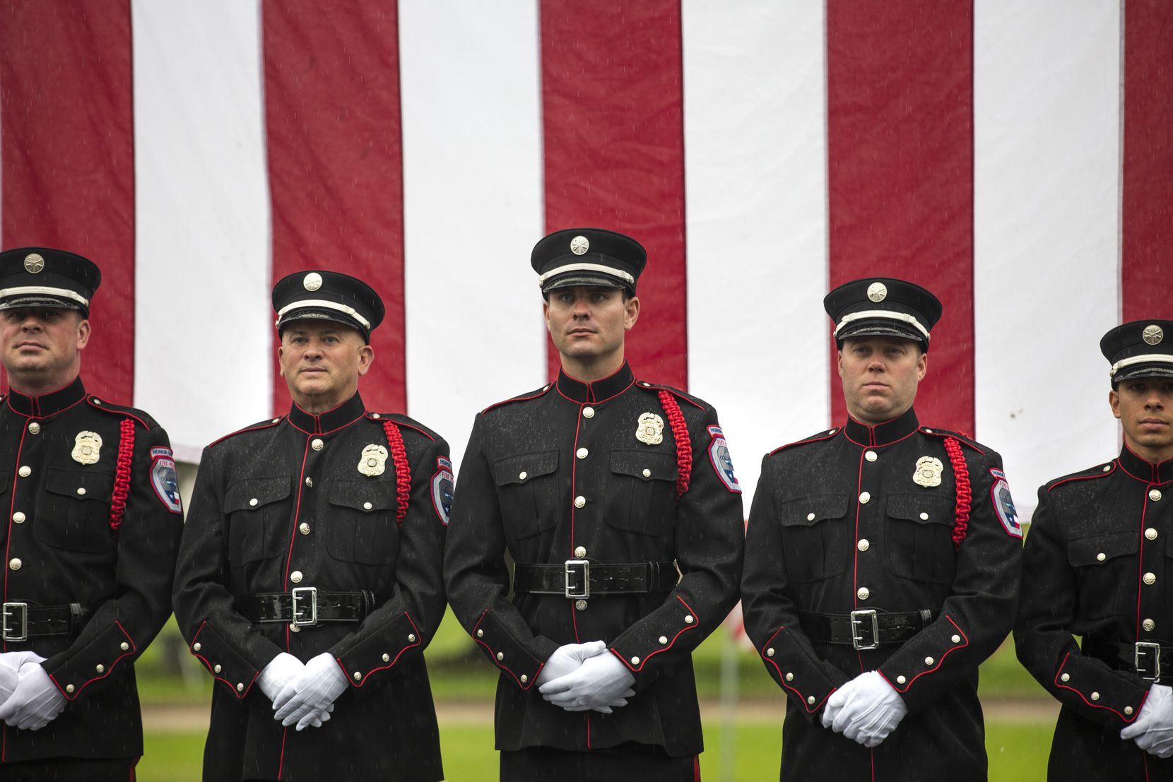Matt Olson (from left), William Savage, Jason Fisch, William Hutton and Martin Mendoza of the Colleyville Fire Department Honor Guard stood next to a large U.S. flag after their participation in a virtual Memorial Day remembrance ceremony at Bluebonnet Hills Funeral Home in Colleyville.