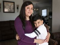 Cynthia Medina, 27, poses for a portrait with her son Aaron Villegas, 8, at her home in West Dallas. After giving birth to another son in May, Medina was able to take a paid maternity leave and later returned to her job at a local nonprofit, often working from home.