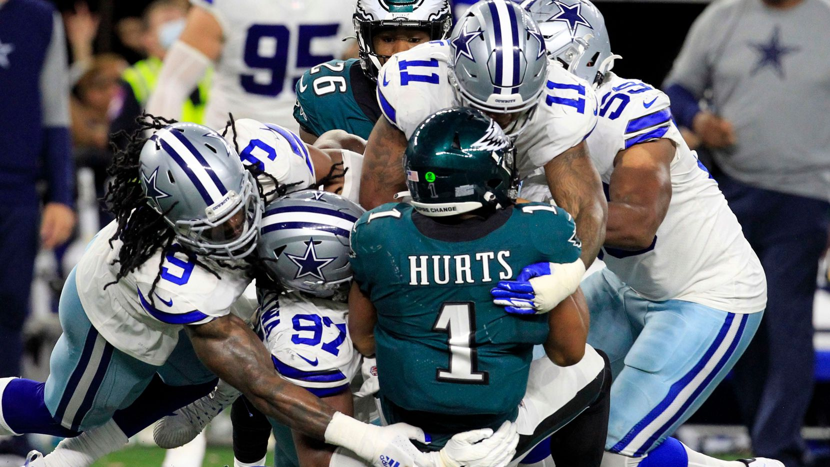 Philadelphia Eagles quarterback Jalen Hurts (1) is swarmed by Dallas Cowboys defenders, including middle linebacker Jaylon Smith (9); defensive tackle Osa Odighizuwa (97), and linebacker Micah Parsons (11) during the second half of a NFL football game at AT&T Stadium in Arlington on Monday, September 27, 2021. (John F. Rhodes / Special Contributor)