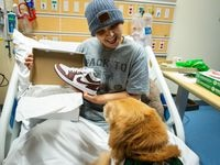 A patient at Children's Health Dallas shows off new shoes to the hospital's comfort dog. The kicks were sent along among other gifts from Dallas Mavericks star Luka Doncic. Development(D211019R): Citali Najera Garcia (grey beanie and shirt, C6).  Professional basketball player, Luka Don  i   of the NBA Dallas Mavericks, donated pizzas, athletic clothing including NIKE brand shoes, and an autographed photo to patients in the Gill Center for Cancer and Blood Disorders (on C7 and D6) at Children   s Health Dallas.