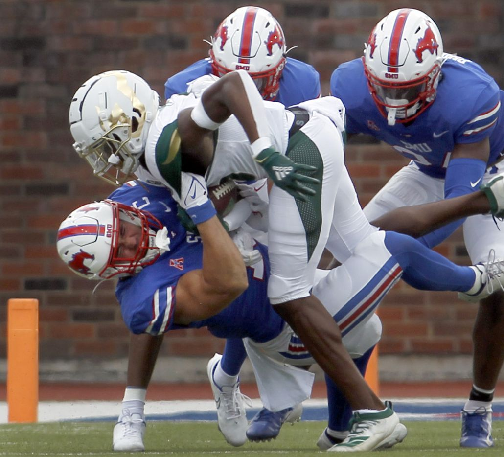 SMU safety Trevor Denbow (16), lower left, wrestles down South Florida receiver Jimmy Horn, Jr. (5) following a short gain from a second quarter reception as more Mustangs defenders move in on the play. The two teams played their NCAA football game at SMU's Ford Stadium in Dallas on October 2, 2021. (Steve Hamm/ Special Contributor)