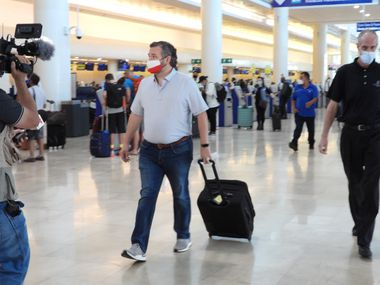 Sen. Ted Cruz checks in for a flight at Cancun International Airport on Feb. 18, 2021, heading back to Houston after one night in Mexico and intense backlash for leaving Texas after a winter storm caused massive power outages.