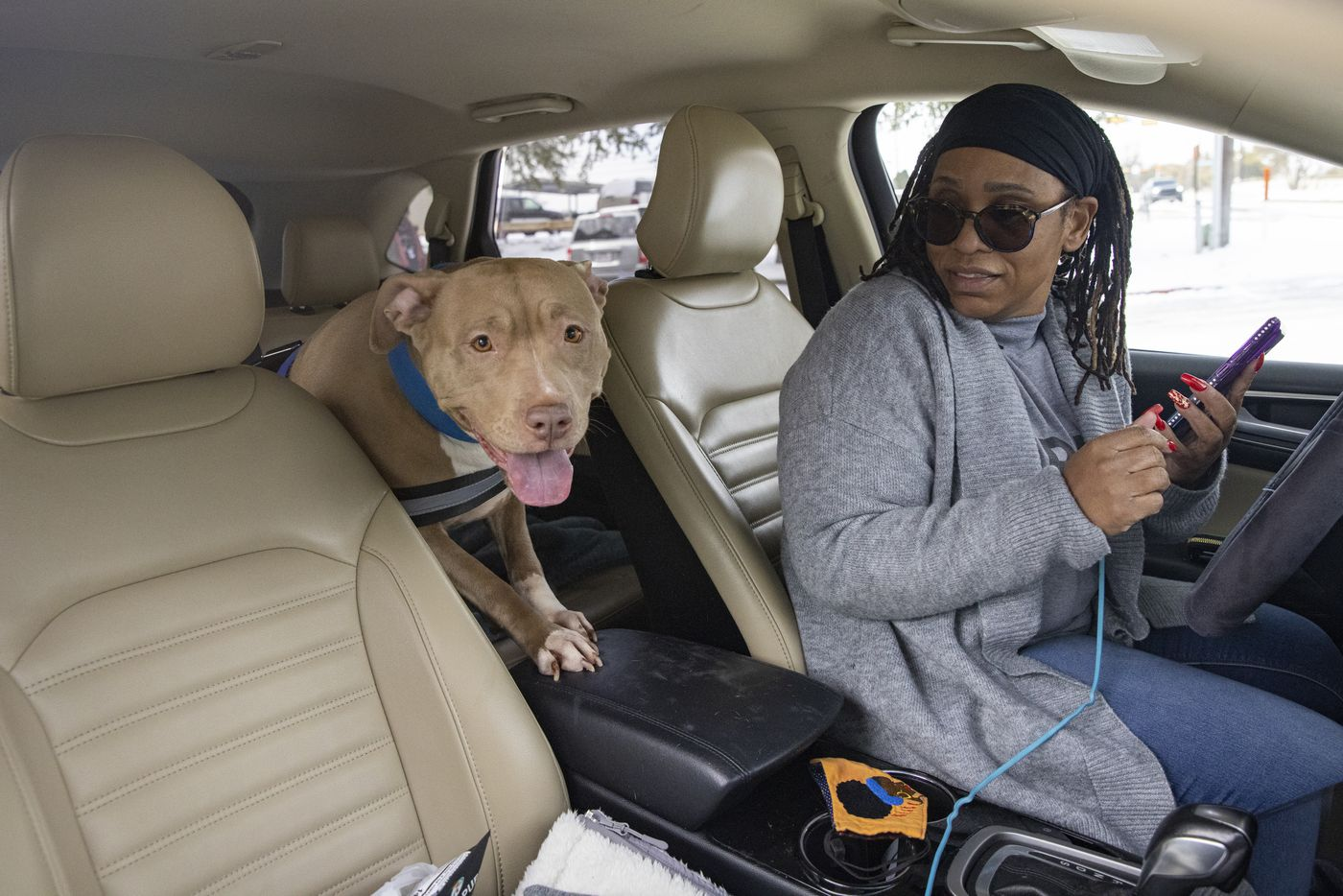 Patricia Ashford from Fort Worth with her dog Sigma makes phone calls after finding out the Motel 6 in North Arlington she reserved two rooms from doesn't have power on Tuesday, Feb. 16, 2021. (Juan Figueroa/ The Dallas Morning News)