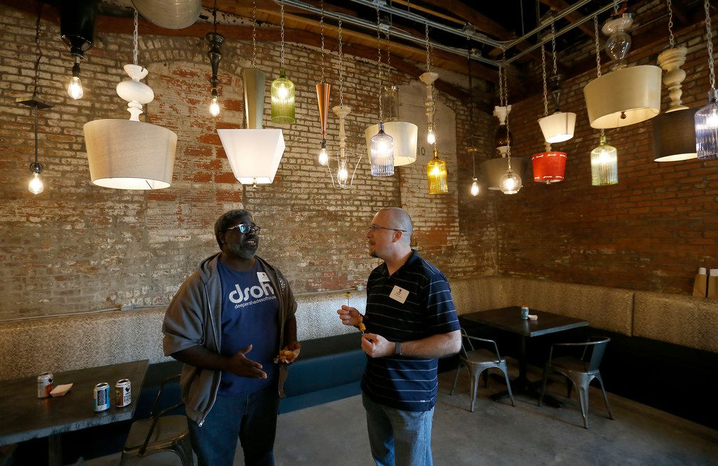 Guests Jerry Richard and Pat St. Jean talk inside the taproom at the new Four Corners Brewing Co. facility in the Cedars neighborhood in Dallas, Wednesday, Oct. 18, 2017.