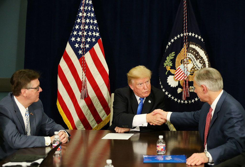 United States President Donald Trump shakes hands with Texas governor Greg Abbott with Texas lieutenant governor Dan Patrick watching on as the President and officials discuss hurricane response at Dalfort Fueling near Love Field in Dallas Wednesday October 25, 2017. President Trump will participate in a hurricane recovery briefing, a Republican National Committee roundtable and give remarks at a reception. (Andy Jacobsohn/The Dallas Morning News)