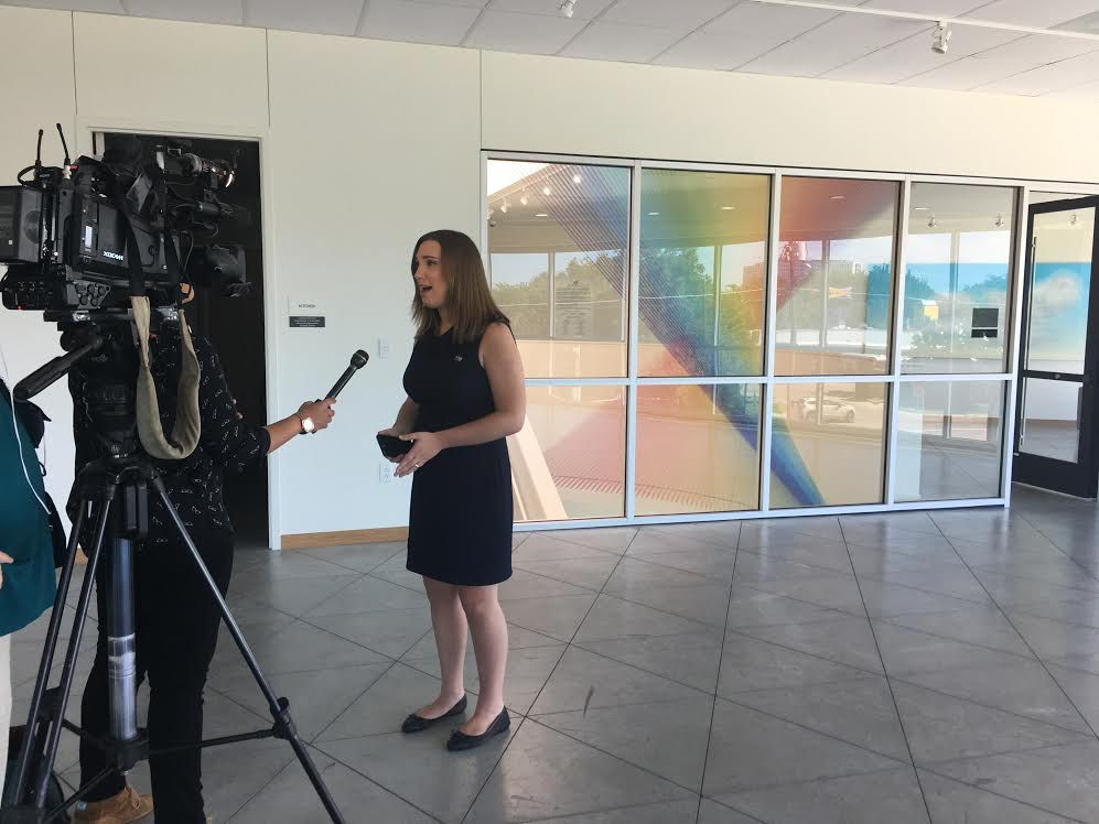 Sarah McBride, national press secretary for the Human Rights Campaign, stands in front of a rainbow art piece in the Dallas Resource Center during an interview after the panel.