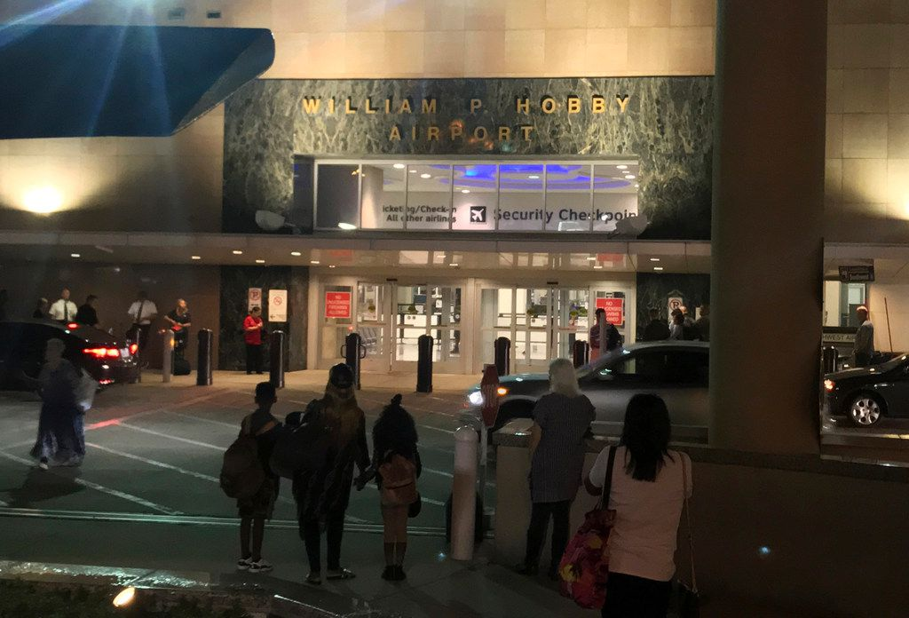 People wait outside Houston's William P. Hobby Airport on Thursday after a toy grenade in a passenger's bag forced the shutdown of a security checkpoint, inconveniencing hundreds of people catching early-morning flights.