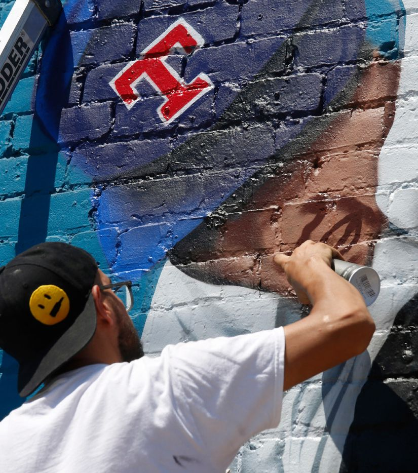 """Dallas-based muralist Isaac """"IZK"""" Davies works on the face of Nolan Ryan on the mural he is painting in Deep Ellum. (Ron Baselice/The Dallas Morning News)"""