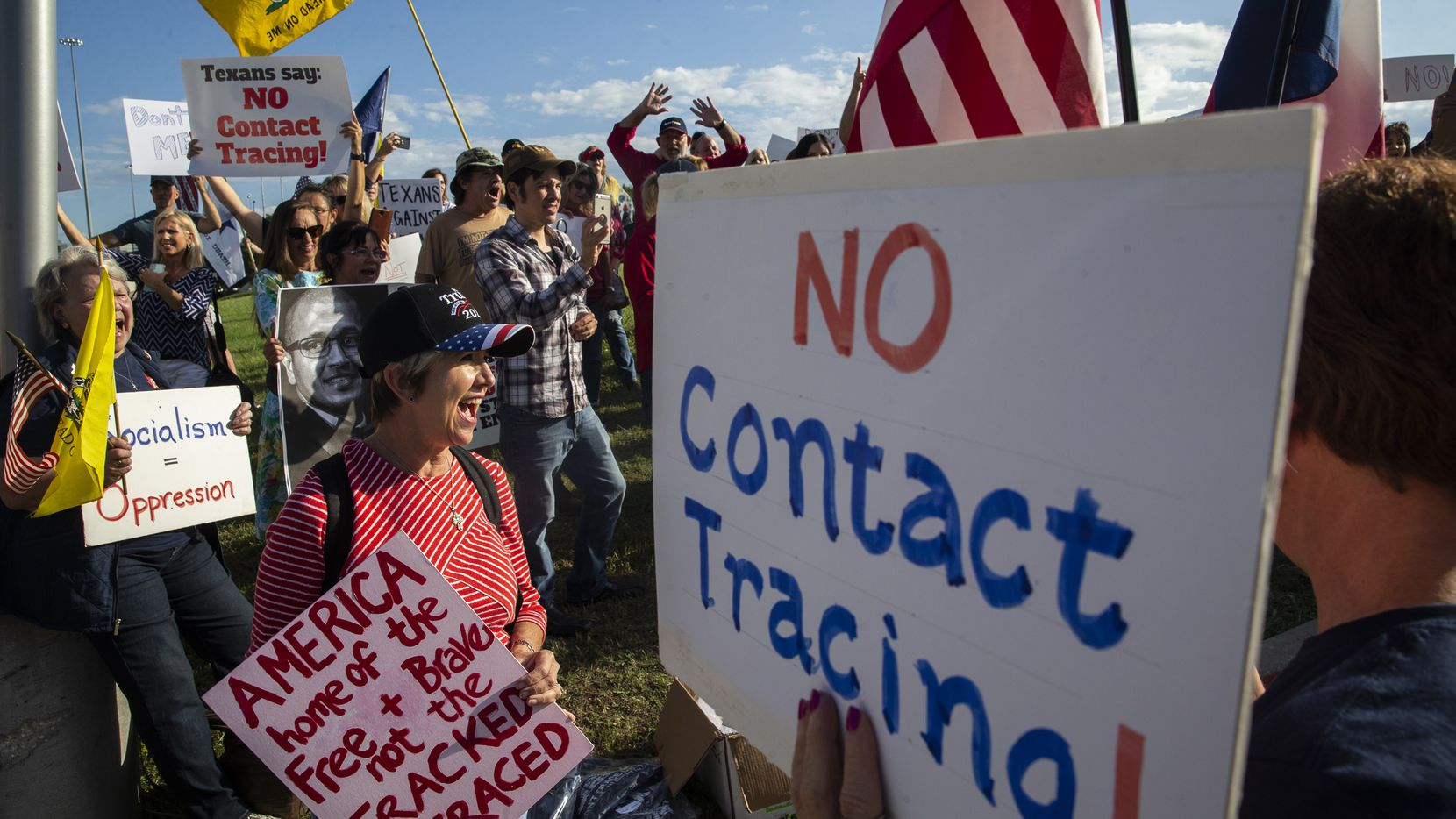 Renata Richardson (center) chants with other demonstrators during a protest organized by Texans Against Contact Tracing outside of the building that houses MTX Group, the company hired by Texas to do contact tracing, in Frisco, Texas, on Tuesday, May 26, 2020. Event organizer Grant Bynum said that the group is upset about the lack of legislative oversight in the $295 million contract granted to MTX to conduct contract tracing for the state. (Lynda M. Gonzalez/The Dallas Morning News)