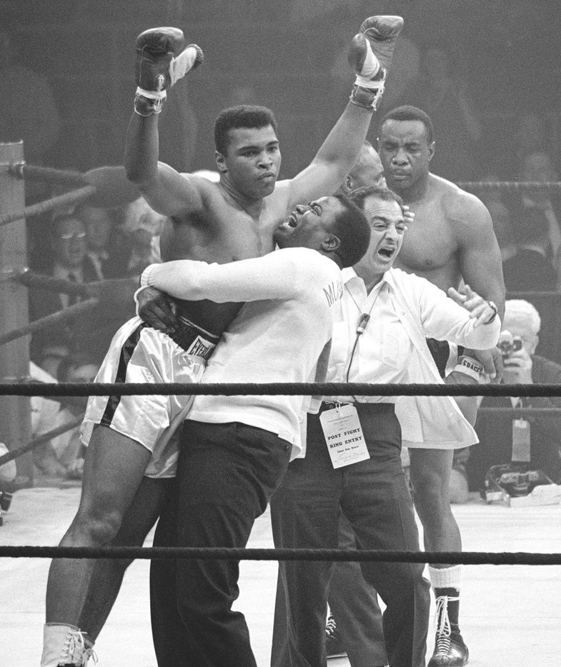 In this May 25, 1965, heavyweight champion Muhammad Ali is lifted in jubilation after his match with boxer Sonny Liston. Clay knocked out Liston in the first round of the match to retain his title.