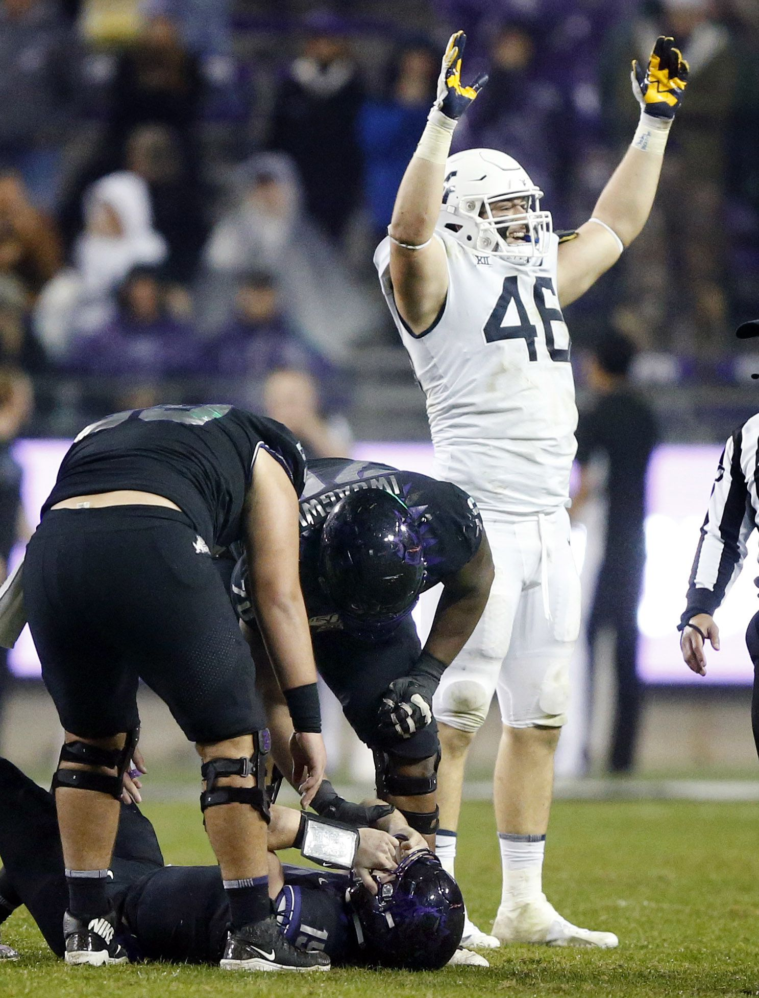 West Virginia Mountaineers defensive lineman Reese Donahue (46) celebrates their win over TCU Horned Frogs quarterback Max Duggan (15, on gorund) at Amon G. Carter Stadium in Fort Worth, Friday, November 29, 2019. Donahue combined for the tackle of Duggan on the last TCU play. TCU lost, 20-17.