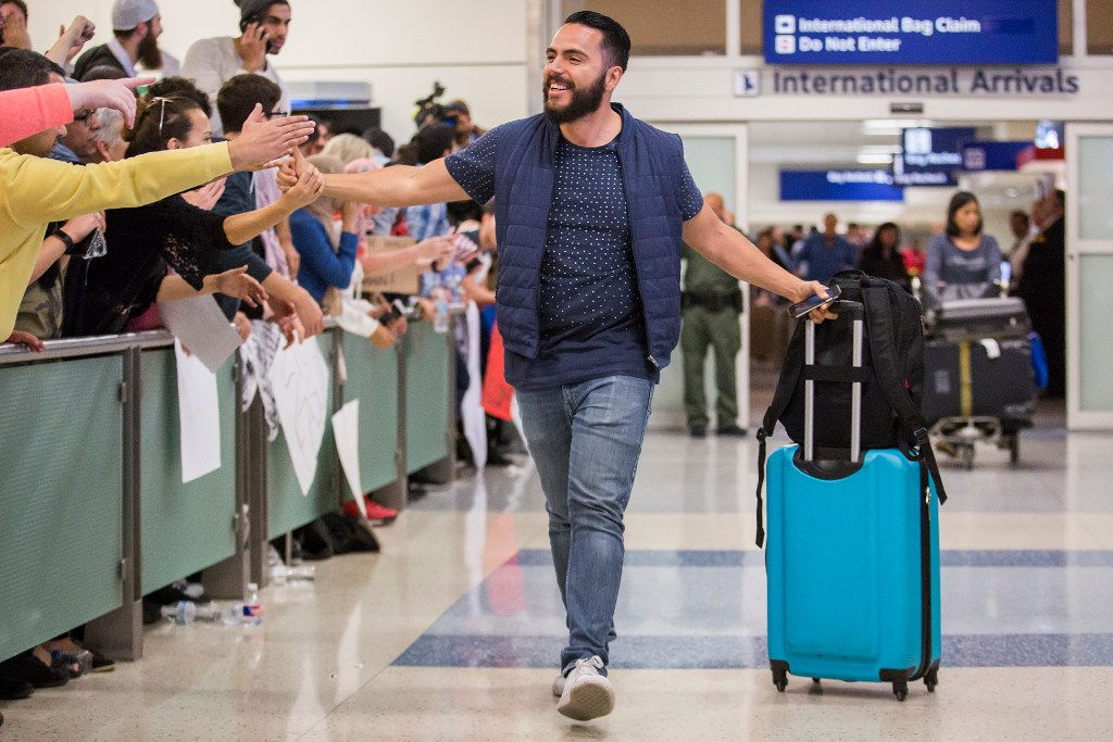 Traveler Alex Galindo high-fives protesters at DFW International Airport holding signs in opposition to President Donald Trump's executive order barring certain travelers as he arrives from Guadalajara, Mexico, on Jan. 29, 2017. Multiple travelers were detained at DFW after Trump shut borders. (Smiley N. Pool/The Dallas Morning News)