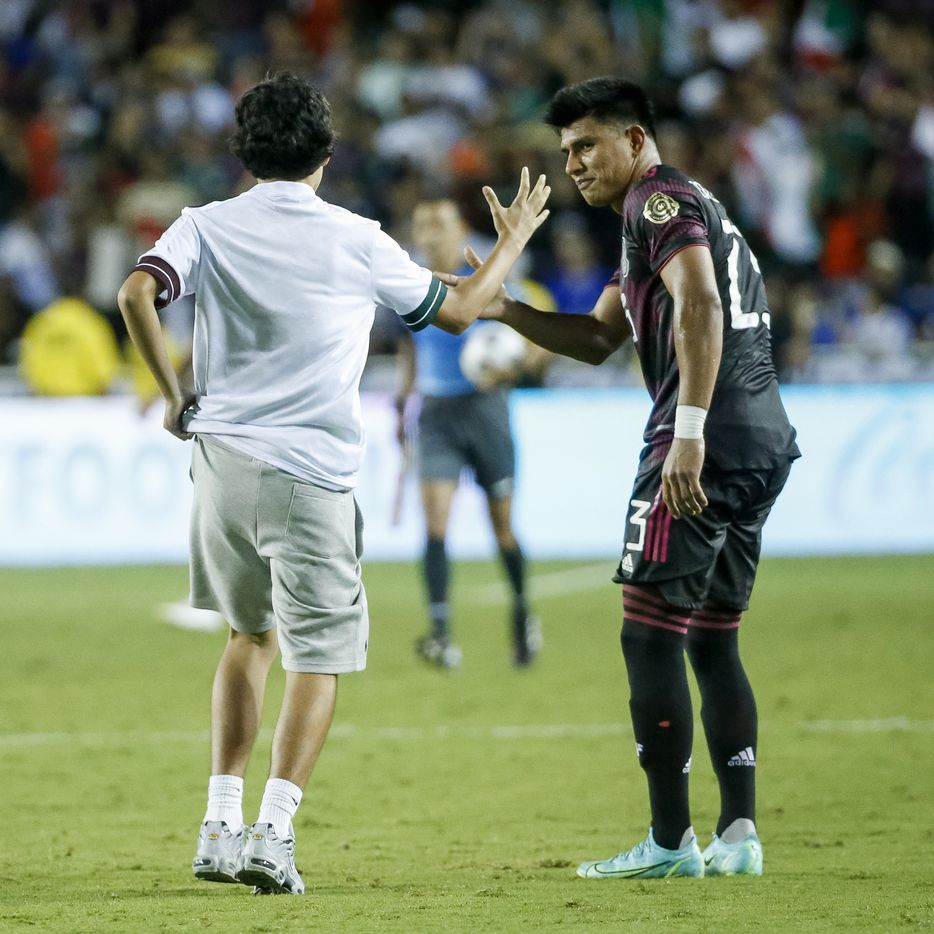 A fan on the field high-fives Mexico midfielder Jesús Gallardo (23) after a CONCACAF Gold Cup Group A soccer match against El Salvador at the Cotton Bowl on Sunday, July 18, 2021, in Dallas. (Elias Valverde II/The Dallas Morning News)