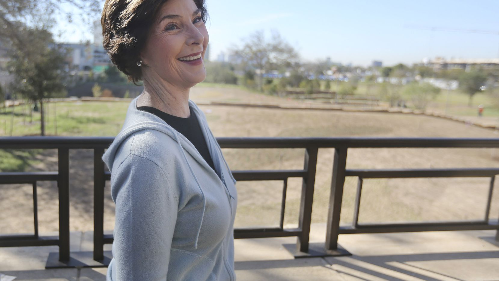 In this Oct. 29, 2012 photo, former first lady Laura Bush smiles during a tour of the George W. Bush Presidential Center in Dallas.  A 15-acre park at the upcoming George W. Bush Presidential Center will recreate a Texas prairie, complete with a wildflower meadow, a special blend of native grasses and even trees transplanted from the former president's ranch. The park's landscaping, which was completed this month, is a recreation of the kind of prairie landscape that would have existed in the area before it the city was built.