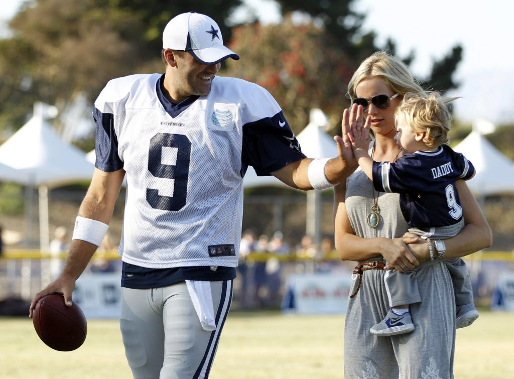 Dallas Cowboys quarterback Tony Romo (9) plays with his son Hawkins Romo, 1, as his wife Candice Romo holds Hawkins after the afternoon practice at Dallas Cowboys training camp in Oxnard, California on July 30, 2013.
