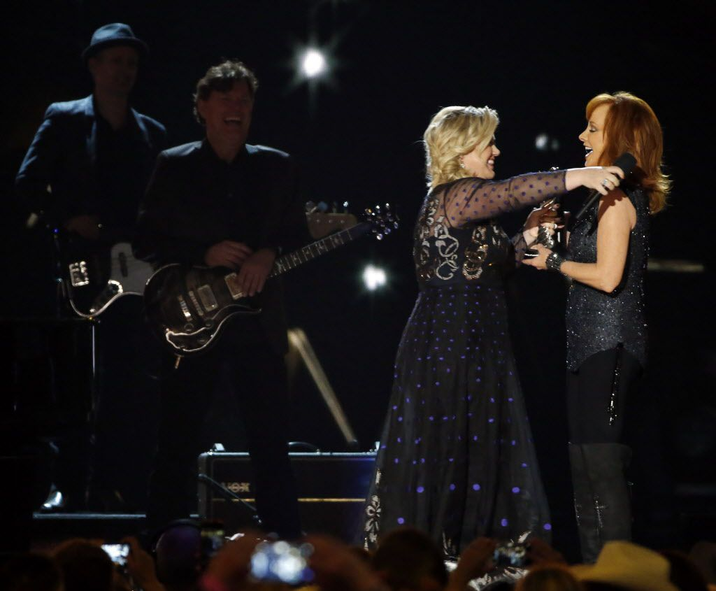 Kelly Clarkson (left) hugs Reba McEntire during the 2015 Academy of Country Music Awards Sunday, April 19, 2015 at AT&T Stadium in Arlington, Texas.