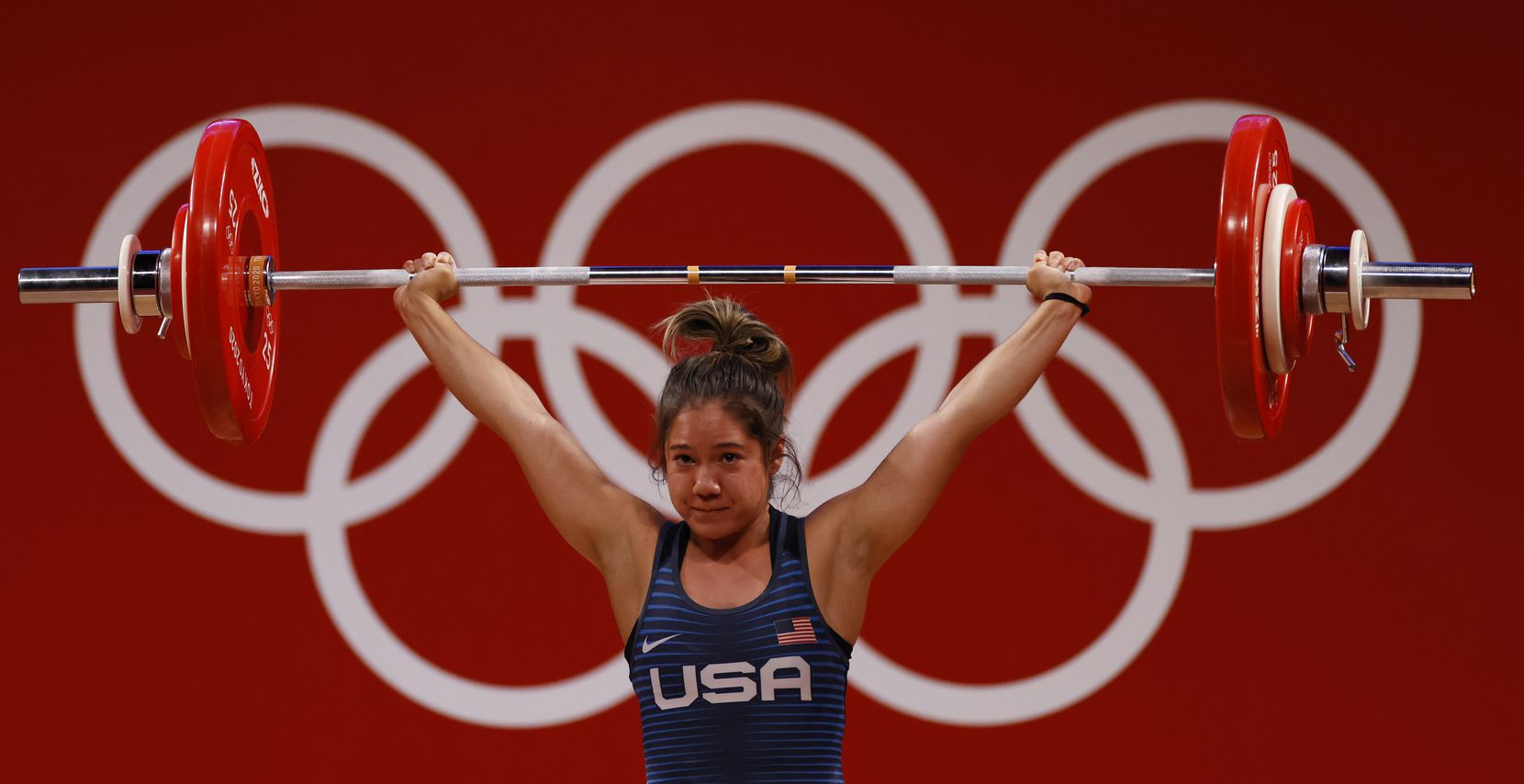 USA's Jourdan Delacruz competes in the first attempt of the snatch round during the women's 49 kg weightlifting final  during the postponed 2020 Tokyo Olympics at Tokyo International Forum on Saturday, July 24, 2021, in Tokyo, Japan.