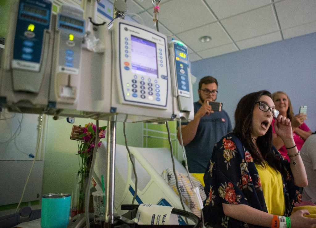 "Danielle Grey, 19, center, reacts to singer-songwriter Cody Johnson as he performs his hit song ""With You I Am"" as Jake Shaw, left, and Shali Farrell record video during a surprise visit by Johnson at Cook Children's Medical Center on Saturday, June 24, 2017, in Fort Worth, Texas. Grey, who was diagnosed with Cystic Fibrosis at 3 months old, was readmitted for treatment causing her to miss Saturday's Cody Johnson concert. (Ryan Michalesko/The Dallas Morning News)"