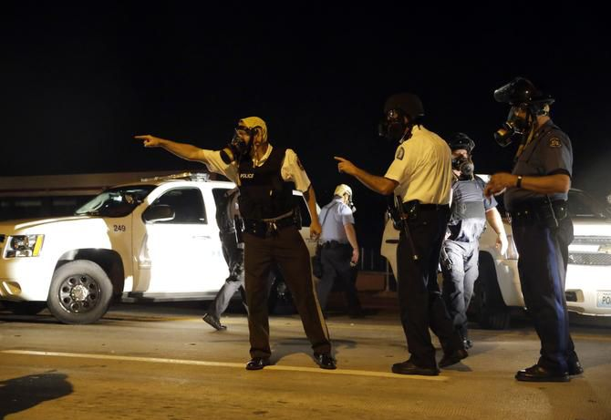 Police take up positions after being shot at Monday in Ferguson, Mo.