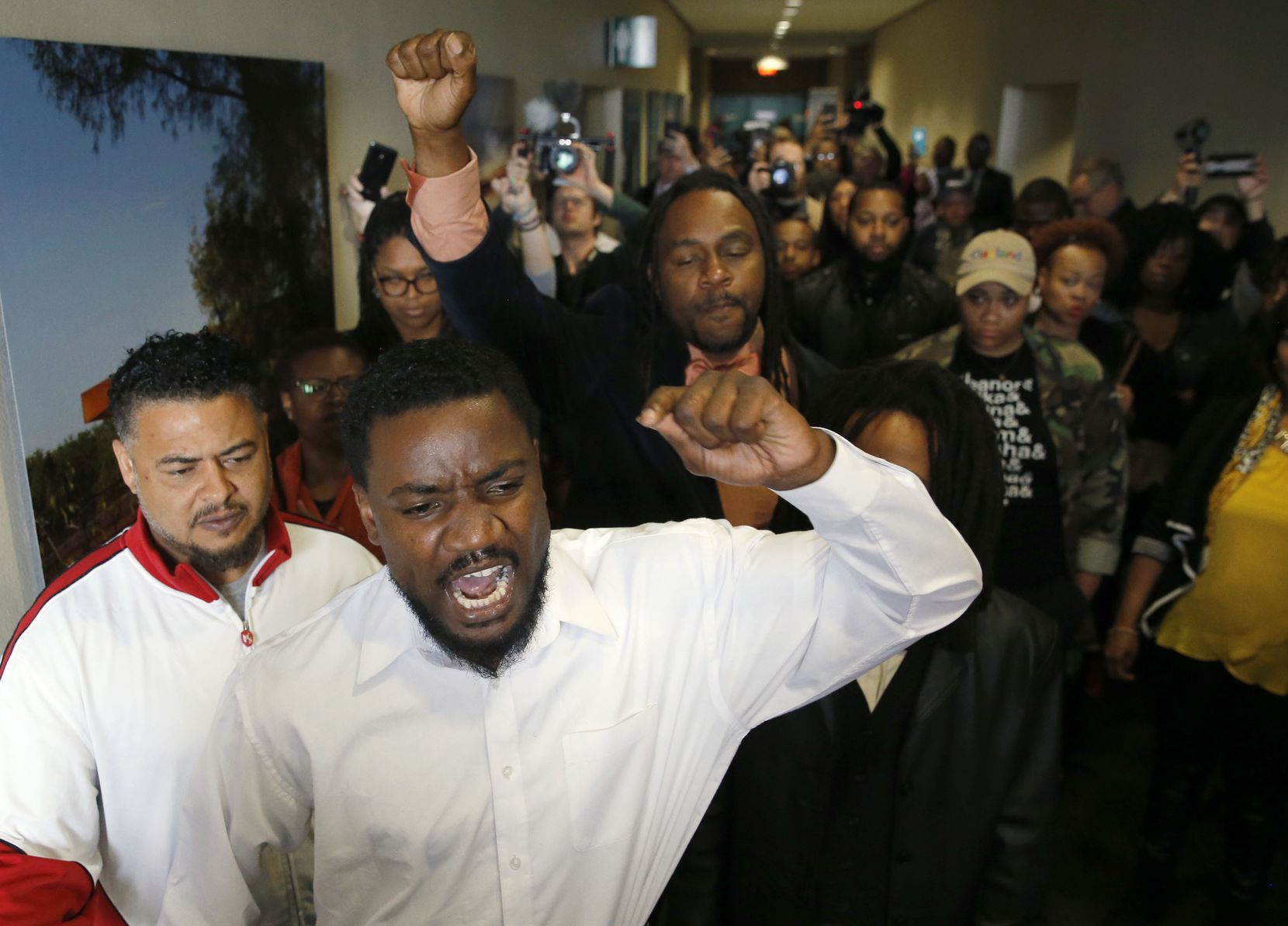 Dominique Alexander (center in white shirt) of Next Generation Action Network leads a protest with others in the hallway of Dallas City Hall in downtown Dallas on Wednesday, April 3, 2019 in Dallas. Alexander and others came to protest a day after a warrant was issued for L'Daijohnique Lee in regards to the Deep Ellum assault with Austin Shuffield.