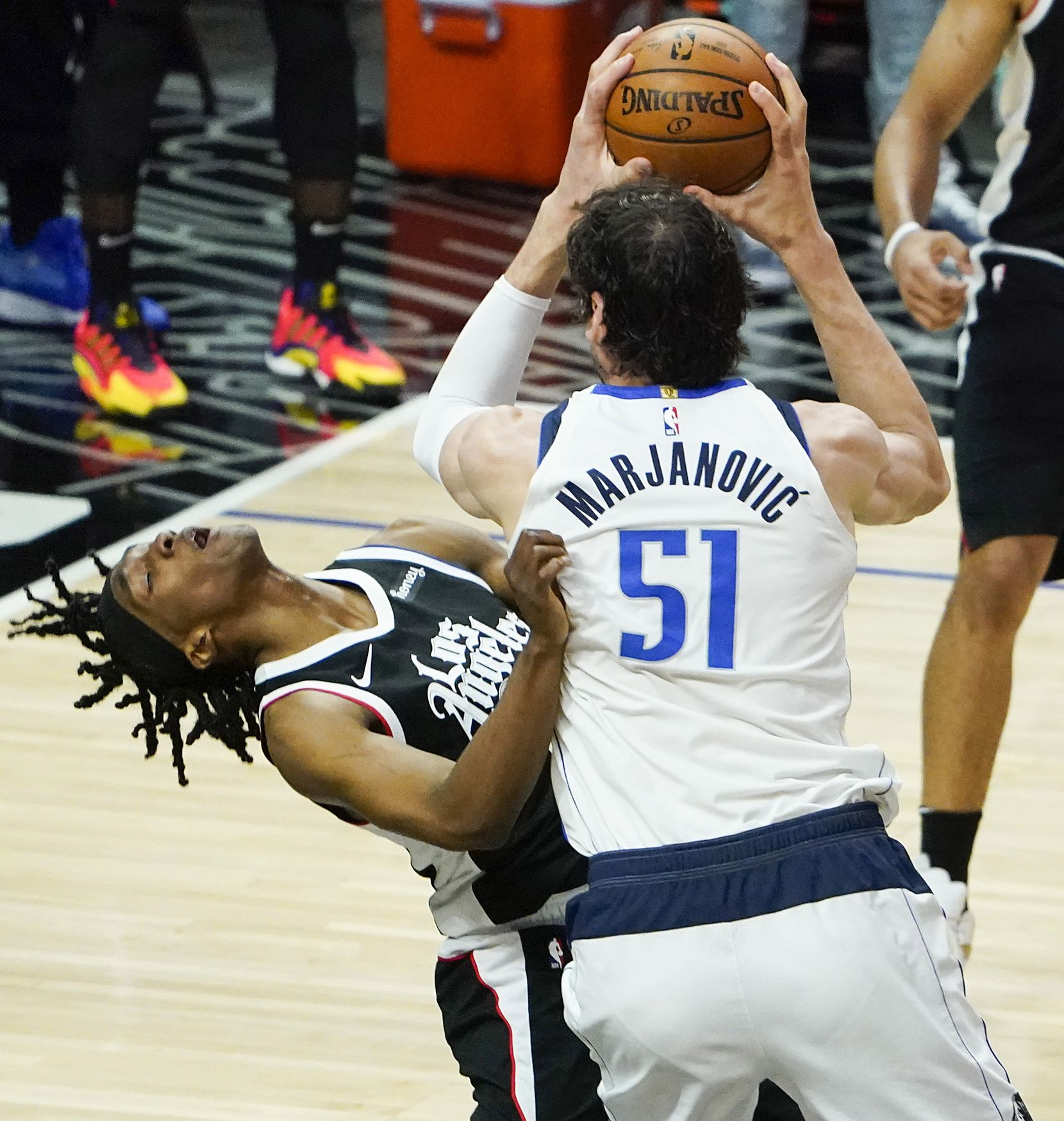 Dallas Mavericks center Boban Marjanovic (51) fouls LA Clippers guard Terance Mann (14) as he goes to the basket during the fourth quarter of an NBA playoff basketball game at the Staples Center on Wednesday, June 2, 2021, in Los Angeles. The Mavericks won the game 105-100. (Smiley N. Pool/The Dallas Morning News)