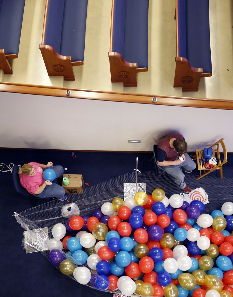 Pam Symank of Texas Balloon Arches and one of her workers, Brent Turner, blow up thousands of balloons Wednesday in advance of First Baptist Dallas' 150th anniversary celebration at the  downtown Dallas church.