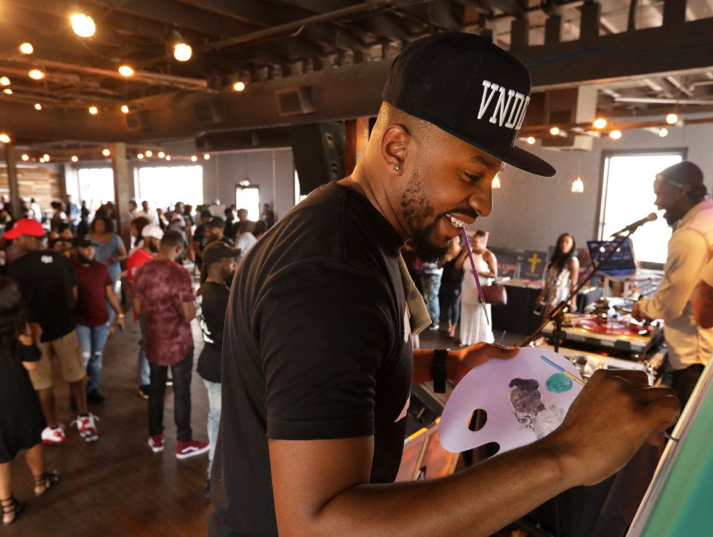 Artist JE the Vandl (real name Joshua Ellis) paints while guests mingle and network at the Good Culture event Bangers & Brunch in Dallas.