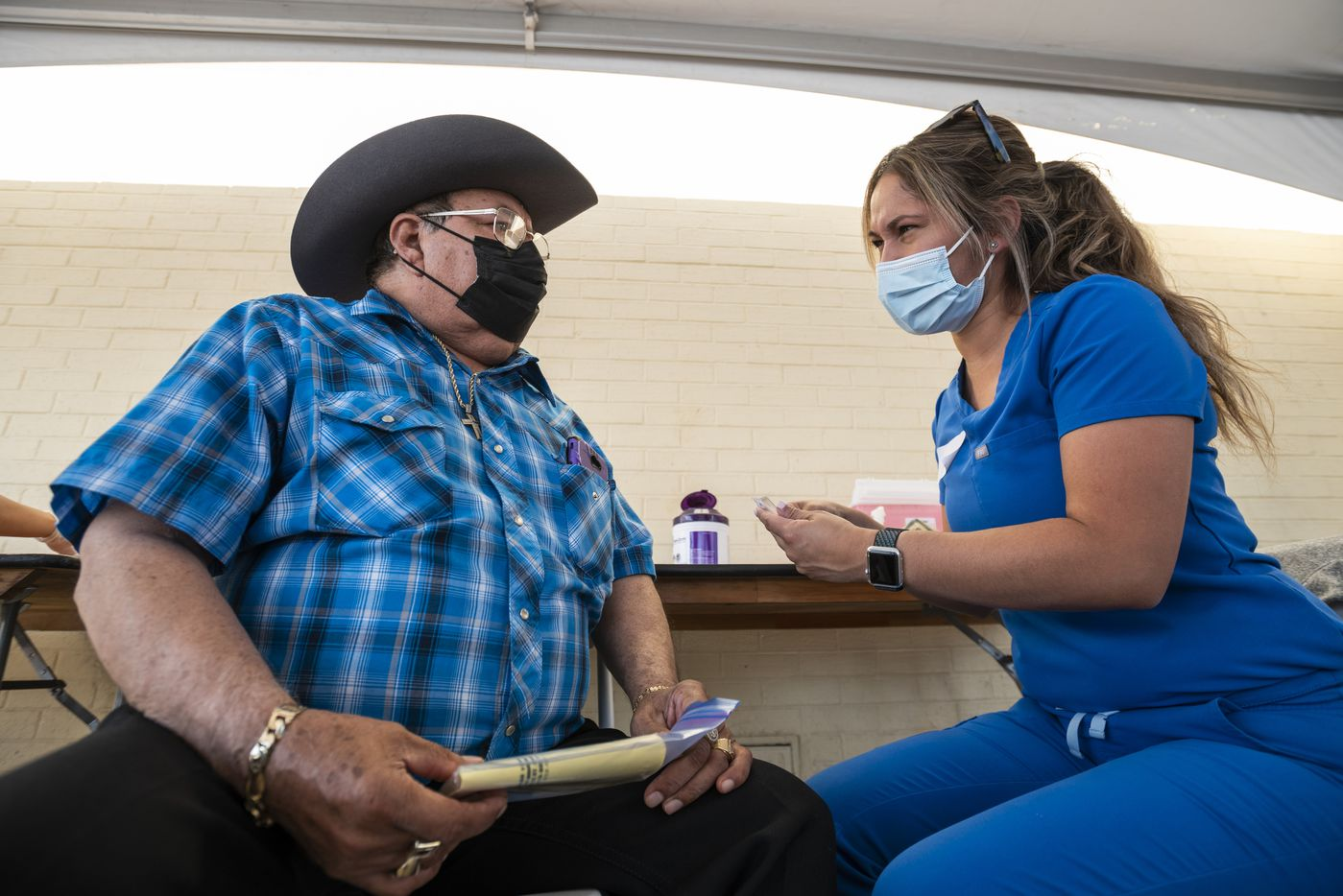Ramon Franco, 68, speaks with registered nurse Lorena Ramirez before receiving his COVID-19 booster at the pop-up clinic.