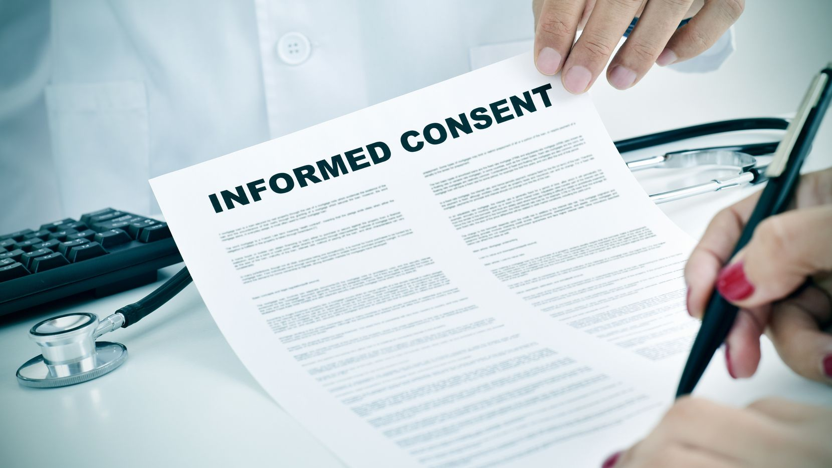 Closeup of a young woman patient signing an informed consent document at the doctor's office.