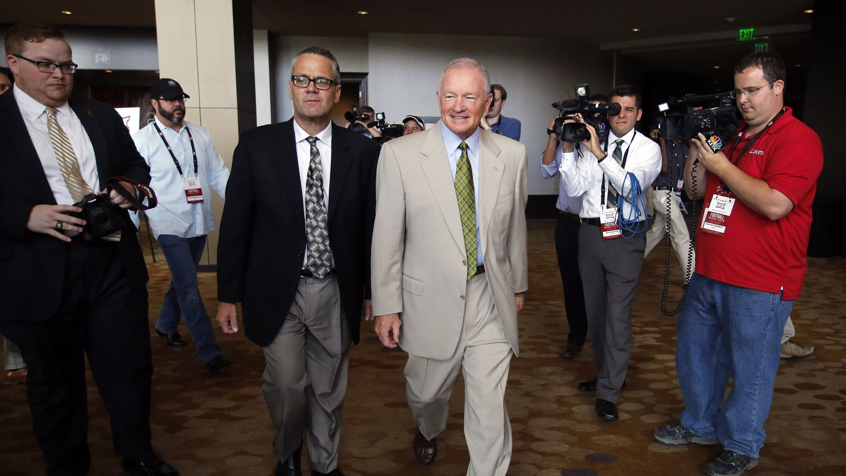 New Baylor head football coach Jim Grobe (center, right) is escorted out of the Big 12 Conference Football Media Days following his Q&A with reporters at the Omni Dallas Hotel, July 19, 2016. (Tom Fox/The Dallas Morning News)