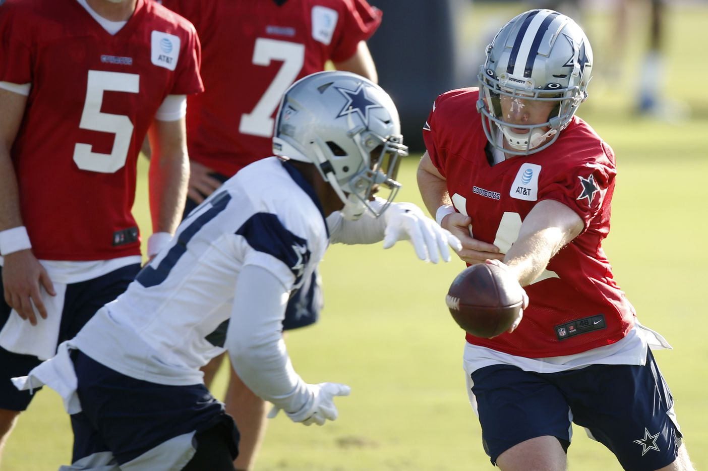 Dallas Cowboys quarterback Andy Dalton (14) hands the ball off to Dallas Cowboys running back Tony Pollard (20) during the first day of training camp at Dallas Cowboys headquarters at The Star in Frisco, Texas on Friday, August 14, 2020. (Vernon Bryant/The Dallas Morning News)