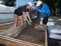 Shelby Espinosa and Charles Spencer filled a GroBox with soil during the expansion of the Hatcher Station Training Farm on Sept. 15. The project will create five jobs and provide fresh food for the community.