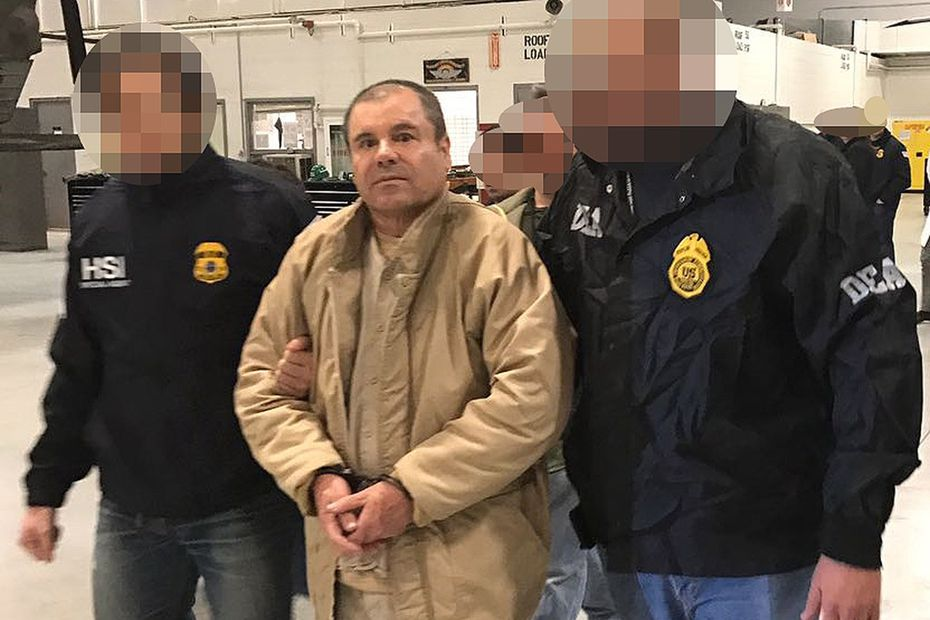 """This file handout photo released by the Mexican Interior Ministry shows Joaquin Guzman Loera aka """"El Chapo"""" Guzman escorted in Ciudad Juarez by the Mexican police as he is extradited to the United States in 2017."""