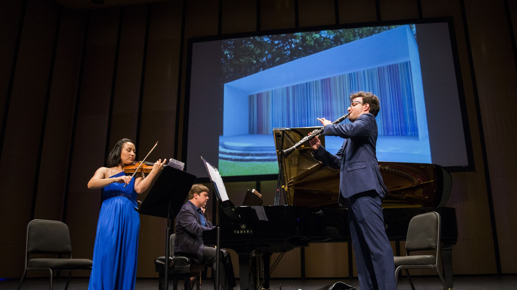 Violinist Grace Kang Wollett, pianist Mikhail Berestnev and clarinetist Danny Goldman rehearse under a photo of 'Horizons,' artwork by Ian Davenport, before a Basically Beethoven Festival concert on July 7, 2019 at Moody Performance Hall in Dallas.