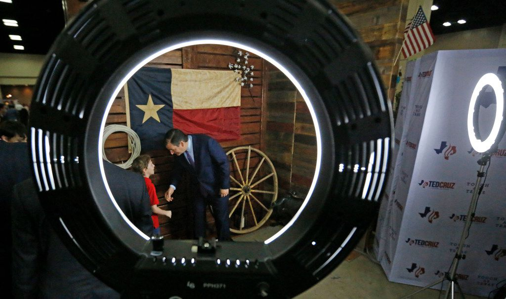 Sen. Ted Cruz talks with Isaac Gebhart of Bedford as he and his family get ready to pose for a photo with the senator during the 2018 Texas GOP Convention.